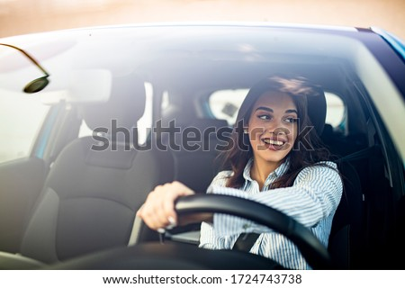 Happy woman driving a car and smiling. Cute young success happy brunette woman is driving a car. Portrait of happy female driver steering car with safety belt #1724743738