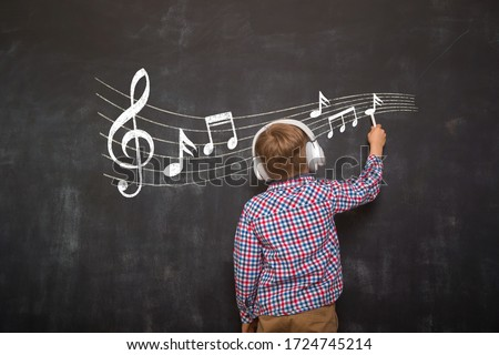 Back view of child boy in headphones drawing music note on blackboard. Music lesson
