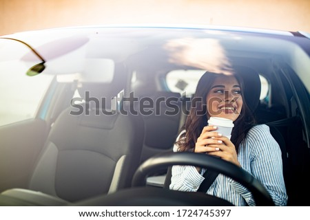 Portrait of a young and cheerful woman with coffee cup driving luxury car in the city. Smiling pretty young woman drinking take out coffee when driving to work in the morning #1724745397