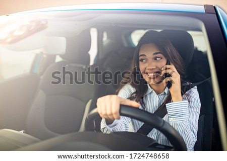 Driver woman driving a car distracted on the phone and looking at side. Young Woman Talking on Mobile while Driving. Young woman driving his car and talking on the phone. #1724748658