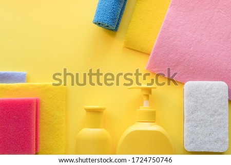 Colorful cleaning set for different surfaces in kitchen, bathroom and other rooms. Empty place for text or logo on yellow background. Cleaning service concept. cleaning items.regular clean up. #1724750746