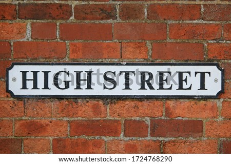 High Street sign in black and white on red brick wall background