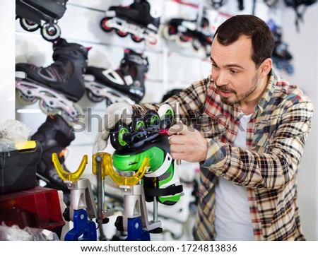 Satisfied  male master fixing roller-skates in sports store #1724813836