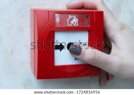 Human hands are pulling red fire alarms on the white walls along the mall corridor.The concept of a picture about fire alarms in buildings. Fire extinguish equipment. Pressing the fire alarm system.