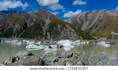 New Zealand landscape with mountains, blue skies and icebergs floating in Tasman Lake, a glacial lake located in Mount Cook National Park on the South Island of New Zealand #1724835397