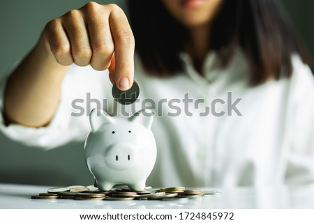 Hand putting coin on pig saving. business, investment, retirement, finance and Money Saving for the future concepts. Royalty-Free Stock Photo #1724845972