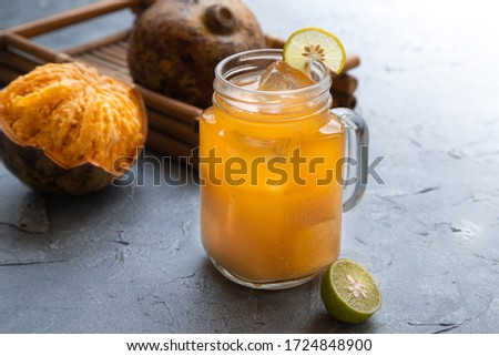 exotic fruit juice from Bel fruit or wooden Apple called in India Bel Ka Sharbat. cold fruit drink with ice, lime and Bel fruit slices on a gray background. natural detox. vitamins for immunity #1724848900