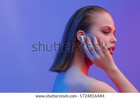 A beautiful young girl in wireless headphones listens to song with a good mood. bright colorful music poster. Royalty-Free Stock Photo #1724856484