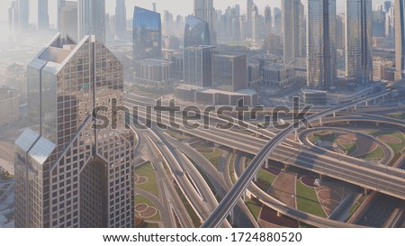 Aerial view of empty highway interchange in Dubai downtown after epidemic lockdown. Cityscapes with disappearing traffic on a bridge and streets. Roads and lanes crossroads without cars, Dubai, United #1724880520