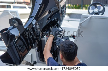 Mechanic is installing speed boat engine , a new engine on an aluminum boat. Royalty-Free Stock Photo #1724895052