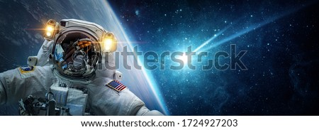 Astronaut in orbit Earth against the background of a falling meteorite, asteroid, comet. Glowing asteroid and tail of a falling comet. The concept on the theme of the apocalypse, armageddon, doomsday. #1724927203