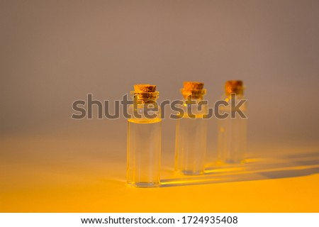 Three glass corked bottles filled with liquid. Background for science and medicine. Virus vaccine. #1724935408