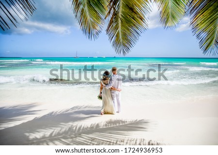 Newlyweds holding hands hugging at white sandy tropical caribbean beach landscape after wedding ceremony of marriage on destination wedding honeymoon travel looking on blue sea in Punta Cana Dominican Royalty-Free Stock Photo #1724936953