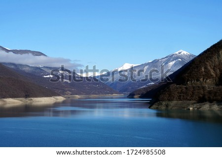 Georgia, Ananuri - January 3, 2018: General view of the Zhinvali reservoir and the snowy Caucasus mountains from the road.                                #1724985508