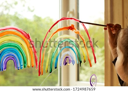 Child at home draws a rainbow on the window during quarantine Covid-19 at home. Stay home, Coronavirus prevention campaign on social networks Flash mob. Hope concept. Chasetherainbow. #1724987659