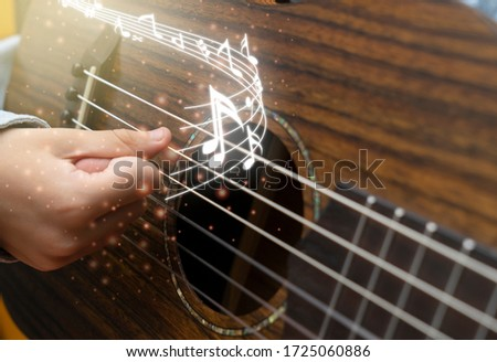 Little boy is playing the guitar with note music #1725060886