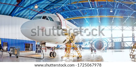 Panoramic view of aerospace hangar, civil aviation aircraft, repair and maintenance of mechanical parts in an industrial workshop Royalty-Free Stock Photo #1725067978