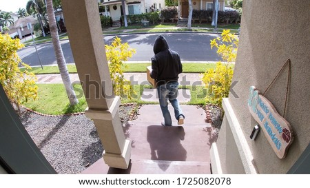 Package thief caught on video doorbell system stealing a box delivery from the front step of a suburban home Royalty-Free Stock Photo #1725082078