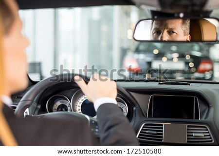 Feeling confident in his new car. Rear view of confident senior man in formalwear sitting on drivers place in car and looking at mirror Royalty-Free Stock Photo #172510580