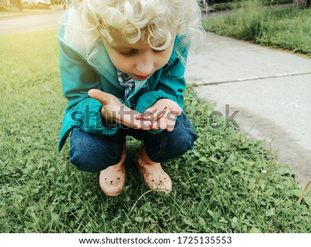 Cute Caucasian preschool girl holding rain worm in hands. Child kid learning studying nature around. Natural biology science. Curious kid playing watching touching a wild animal outdoors.