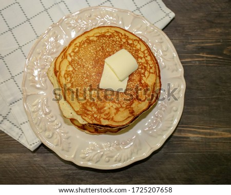 Top view of stack of pancakes or hotcakes with butter on top.