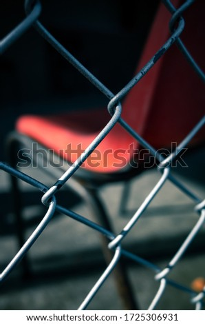 Orange seat behind a fence #1725306931