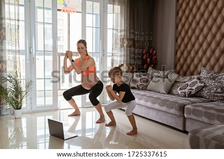 Pregnant woman and kid in sport clothing exercising at home. Online training during coronavirus covid-19 quarantine. Stay fit and safe during pandemic lockdown. Sport, fitness, healthy concept #1725337615