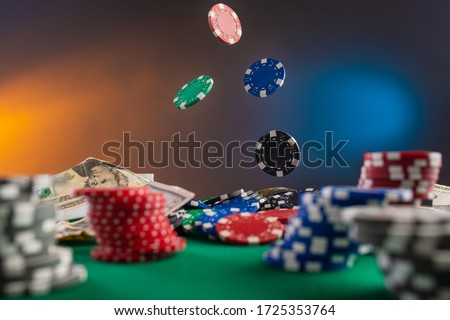 Online gaming business, casino, poker. Flying, levitating chips against the background of a poker table, money and chips. Creative light. Background for the casino gaming business. #1725353764