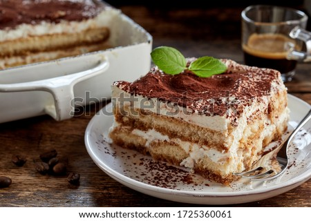 Close up on a portion of gourmet tiramisu Italian dessert topped with a sprig of mint served on a plate at table in a side view #1725360061