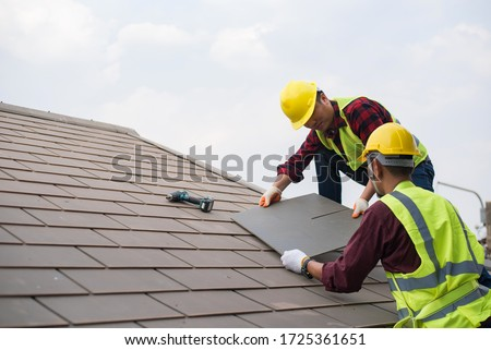 Gray roof - Repair and replace the roof of the house with Handyman with tools and protective equipment. Standing on the roof with the sky background Two Asian male roof mechanic #1725361651