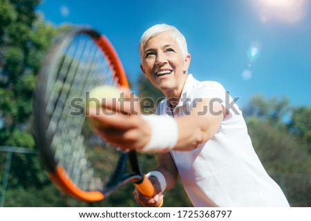 Smiling Elderly Woman Playing Tennis as a Recreational Activity Royalty-Free Stock Photo #1725368797