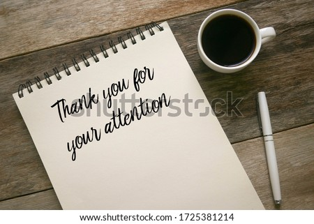 Top view of coffee,pen and notebook written with statement of Thank you for your attention on wooden background. Royalty-Free Stock Photo #1725381214