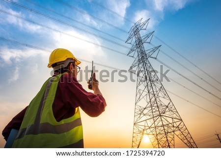 Picture of an electrical engineer standing and watching at the electric power station to view the planning work by producing electricity at high voltage electricity poles. #1725394720