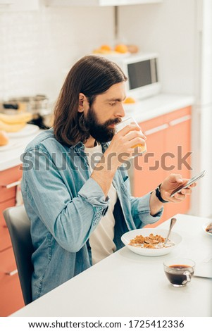 Calm handsome man at home at the kitchen table looking at the screen of his smartphone and holding a glass of juice #1725412336