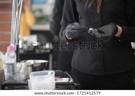 Female hands of a girl in a black uniform clean professional tools after the procedure of permanent makeup of eyebrows in the interior of the salon. Set of hairdressing tools of choice. #1725412579