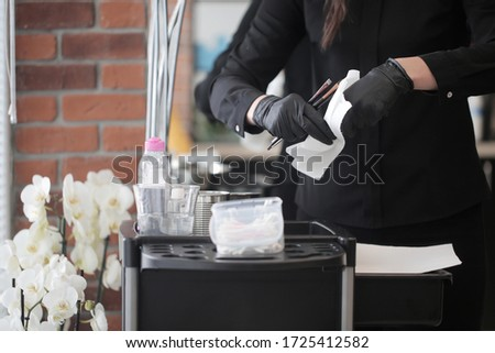 Female hands of a girl in a black uniform clean professional tools after the procedure of permanent makeup of eyebrows in the interior of the salon. Set of hairdressing tools of choice. #1725412582