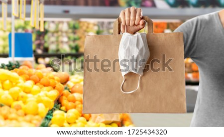 health protection, safe shopping and pandemic concept - close up of woman with paper bag and face protective medical mask over grocery store or supermarket on background #1725434320