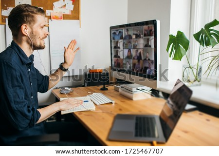 Business video conferencing. Young man having video call via computer in the home office. Multiethnic business team. Virtual house party. Online team meeting video conference calling from home #1725467707