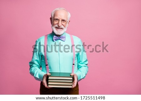 Never late study concept. Photo of amazing aged hipster grandpa hold many books hands elderly student wear specs mint shirt suspenders bow tie pants isolated pastel pink color background