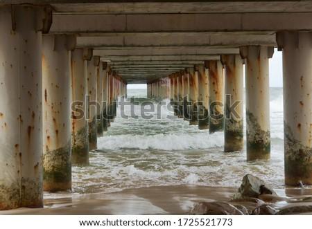 under the bridge, the sea water under the pier, the support of the sea promenade #1725521773