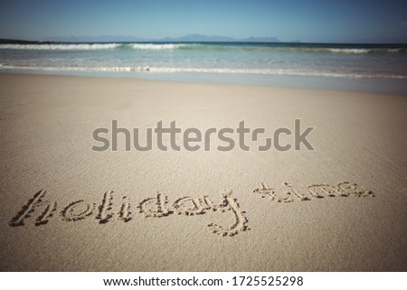 Holiday time drawn on the sand at the beach #1725525298