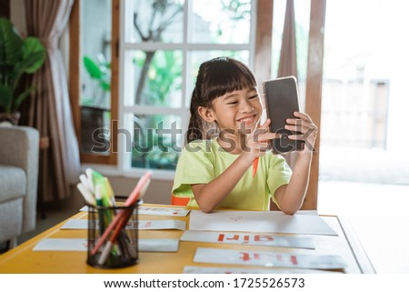 little girl studying from home during self isolation. learning using conference call via smartphone #1725526573