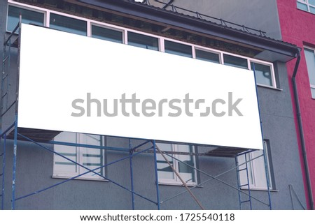 building scaffolding with large advertising banner near facade of repairing house on modern city street