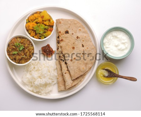 vegetarian Indian thali or Indian home food with lentil dal, cauliflower curry, roti or Indian flat bread, ghee butter, lemon pickle, rice, curd or yogurt #1725568114