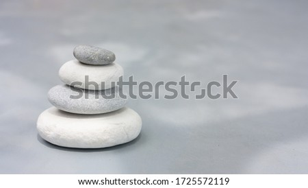 Four grey roundstones on clear gray background. Spa stones, zen like concept. Pastel colors. #1725572119
