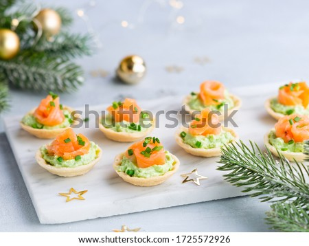 Holidays appetizer canapes with salmon avocado cream cheese on a light background with Christmas decorations. Festive table recipe ideas for New Year's and Christmas holidays. #1725572926
