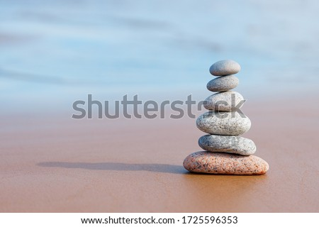 Pyramid stones balance on the sand of the beach. The object is in focus, the background is blurred. Royalty-Free Stock Photo #1725596353