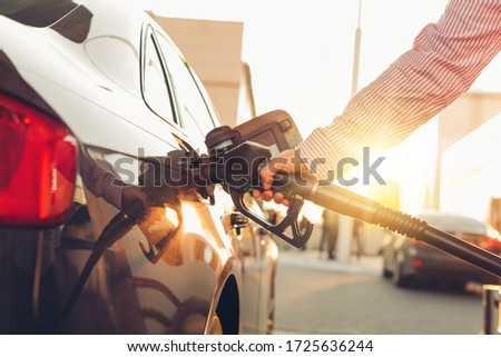 Man handle pumping gasoline fuel nozzle to refuel at petrol station. Transportation and ownership concept. Sunset lighting Royalty-Free Stock Photo #1725636244