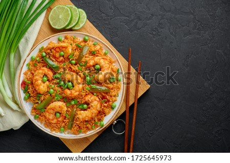 Thai Tom Yum Fried Rice or Prawn Biryani in white plate on black slate backdrop. Tom Yum Fried Rice is Thailand cuisine dish with jasmine rice, shrimps and vegetables. Thai Food. Copy space. Top view #1725645973