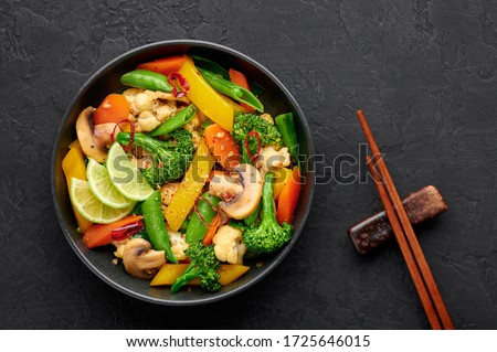 Pad Pak Ruam or Veg Thai Stir-Fried Vegetables in black bowl on dark slate backdrop. Pad Pak is thailand cuisine vegetarian dish with mix of vegetables and sauces. Thai Food. Top view Royalty-Free Stock Photo #1725646015